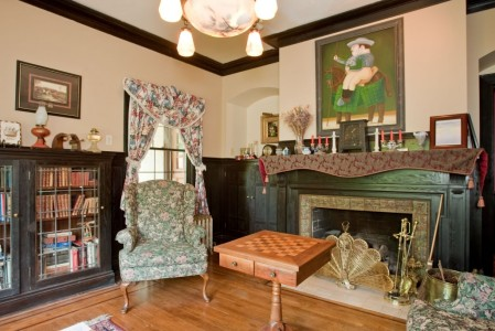 A sitting room with a green chair, black bookcase and brown checkerboard at the Bacon Mansion.