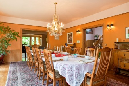A dining room with light brown walls and white cream ceiling set for 12 at the Bacon Mansion.