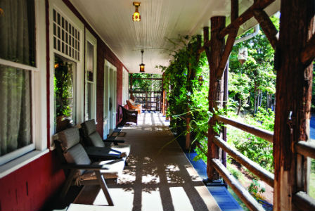 Easy chairs line the exterior corridor of the Gatewood Bed and Breakfast, with green vines lacing the brown wooden rails.