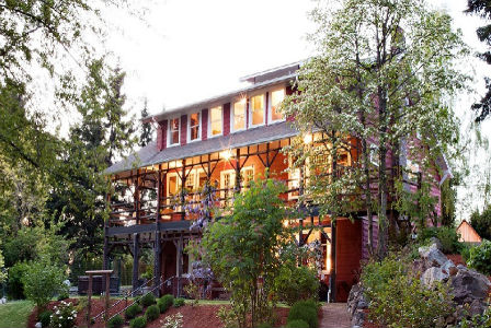 The three-story facade of the Gatewood Bed and Breakfast, nestled amidst green foliage.