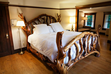 A bed with plush white pillows and bedding atop a driftwood bedframe at the Gatewood Bed and Breakfast.