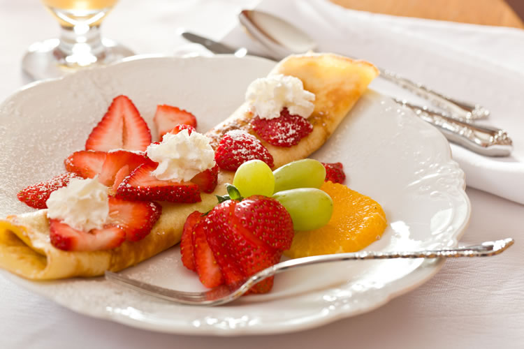 Red strawberries and green grapes sit atop a crepe on a white plate at the Greenlake Guest House.