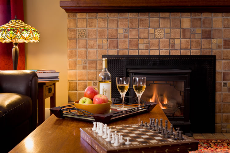 A tray of a bottle of white wine and two glasses and red and green apples sits between a chess set and a fireplace at the Greenlake Guest House.
