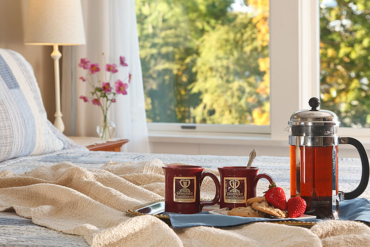 A tray of burgundy mugs and a French press coffee set sits on a bed at the Greenlake Guest House.