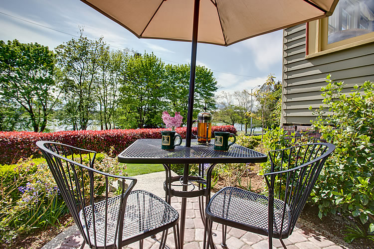 A black metal table and chairs sits under a brown umbrella amidst green foliage at the Greenlake Guest House.