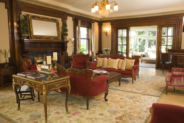 Red upholstered couches with white throw pillows rest on beige carpeting in a sitting room.