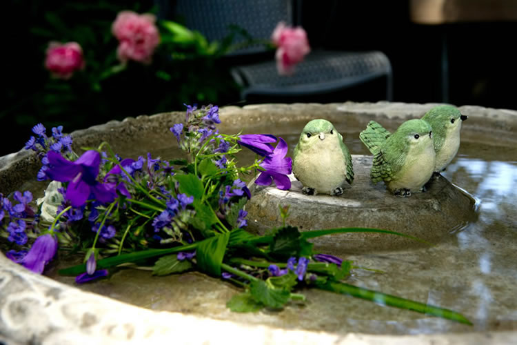 A birdbath with three green and white plumagged birds and purple flowers.