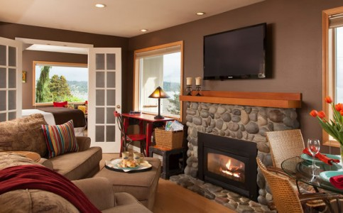 A living room with beige couches and wall with TV mounted over a stone hearthed fireplace at the Three Tree Point B&B.