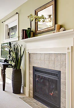View of tiled fireplace with mantel, with green plant and flat screen TV off to the left of the scene