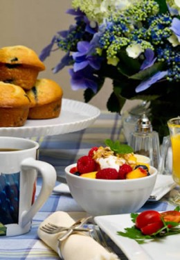 Close up view of a breakfast table setting, colorful fresh fruit, flowers and muffins