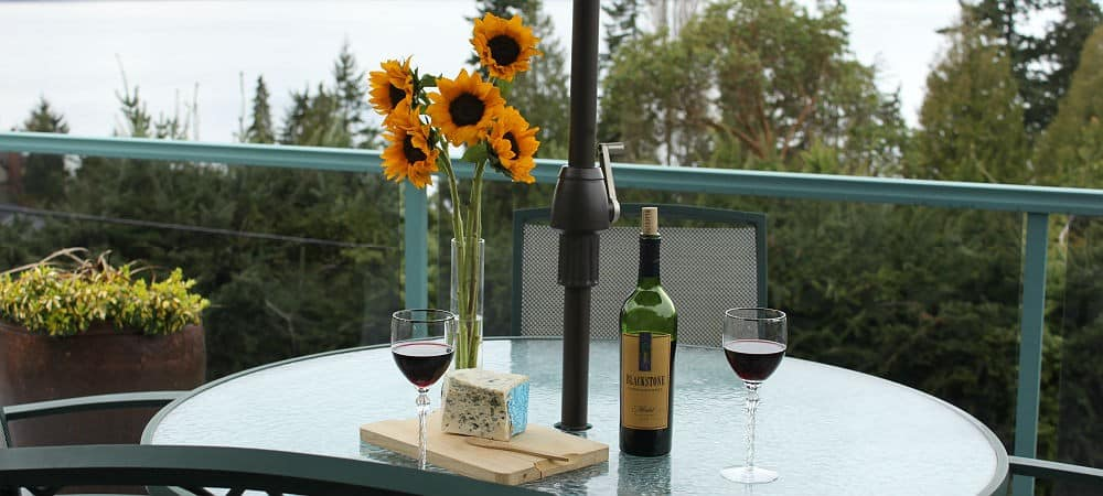 Glass table with a bottle of wine, two wine glasses, blue cheese, and a vase of yellow sunflowers.