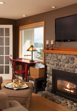 Stone fireplace with an orange fire glowing within and TV above the mantle..