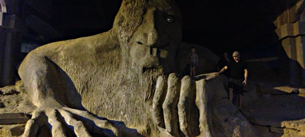 A man stands beside a large beige sculpture of a sand monster.