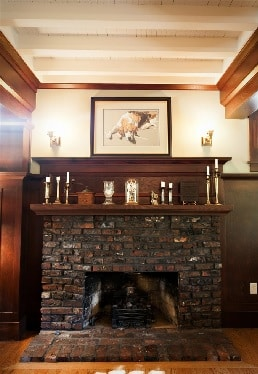 brick fireplace with large wooden mantle