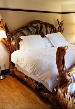 Bed made of wood branches, highly polished with soft puffy white bedding
