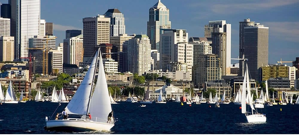 sailboat with full sails in harbor with seattle shoreline in background