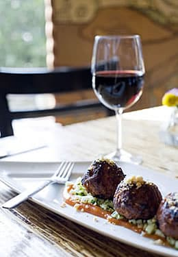 A glass of red wine sits behind a white platter holding meatballs over sauce and a fork.