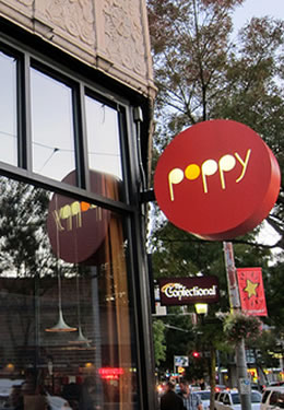 An outdoor restaurant with a red sign that reads Poppy in white and orange lettering.
