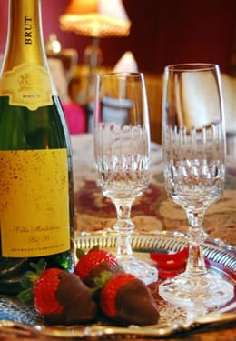 A bottle of Brut champagne sits on a silver platter with two glasses and three brown chocolate covered red strawberries.