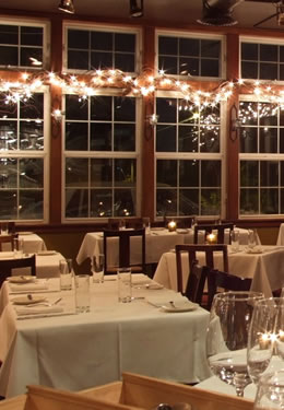 A table for four with a white tablecloth in a room with large windows and white, decorative lights.