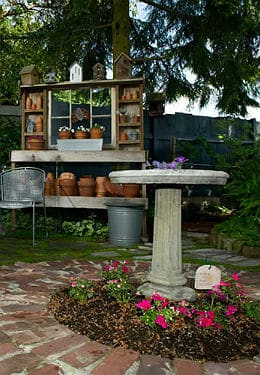 Grey stone bird bath surrounded by pink flowers and wooden shelves behind it with teracotta pots filled with white flowers.